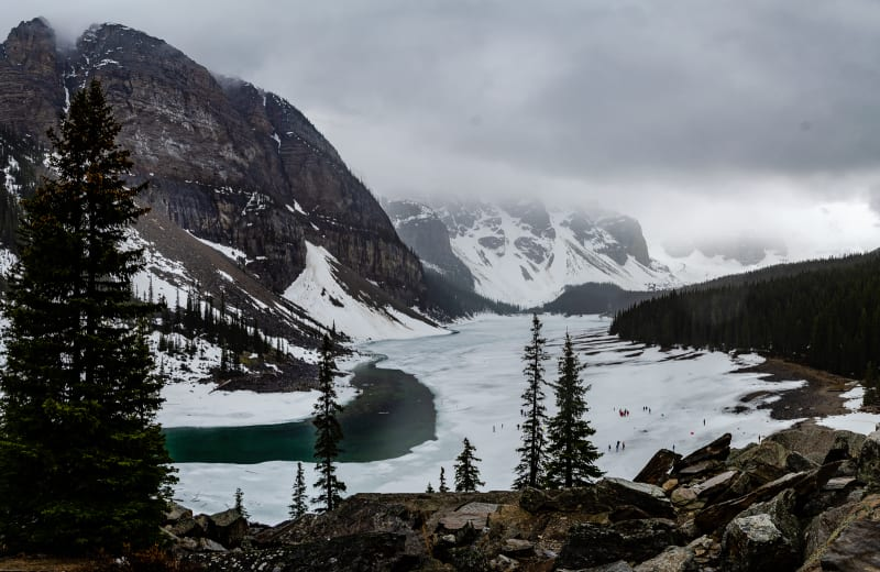 moraine lake covered in ice and snow on a foggy rainy day