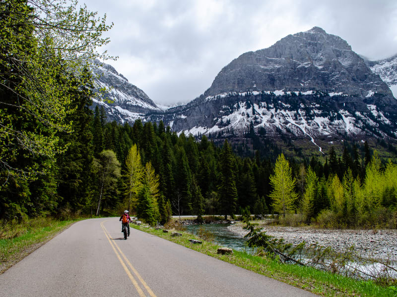 sushila riding along Going-to-the-Sun road with mountains above