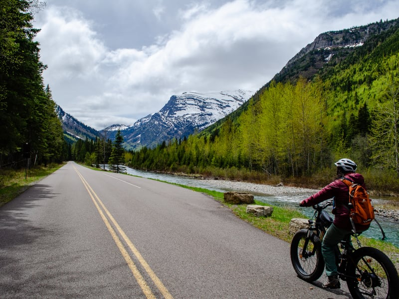 sushila riding on Going-to-the-Sun road with mcdonald creek running along the road
