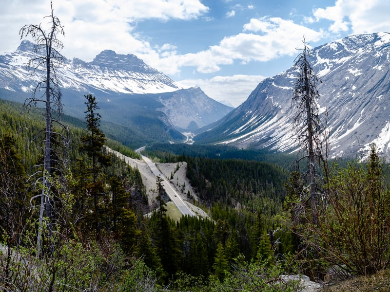 looking down through a valley from the top of a mountain pass along the icefields parkway