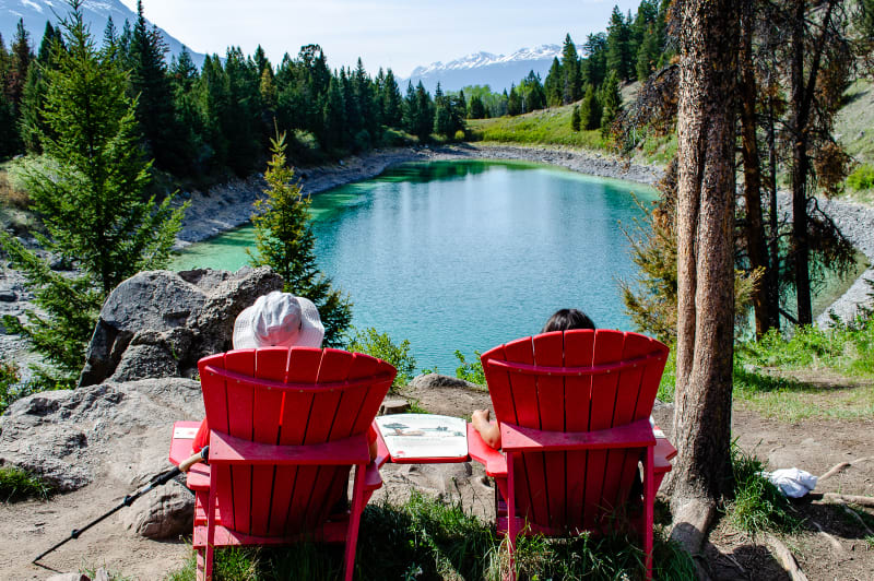 will and sushila sitting in red chairs overlooking a lake