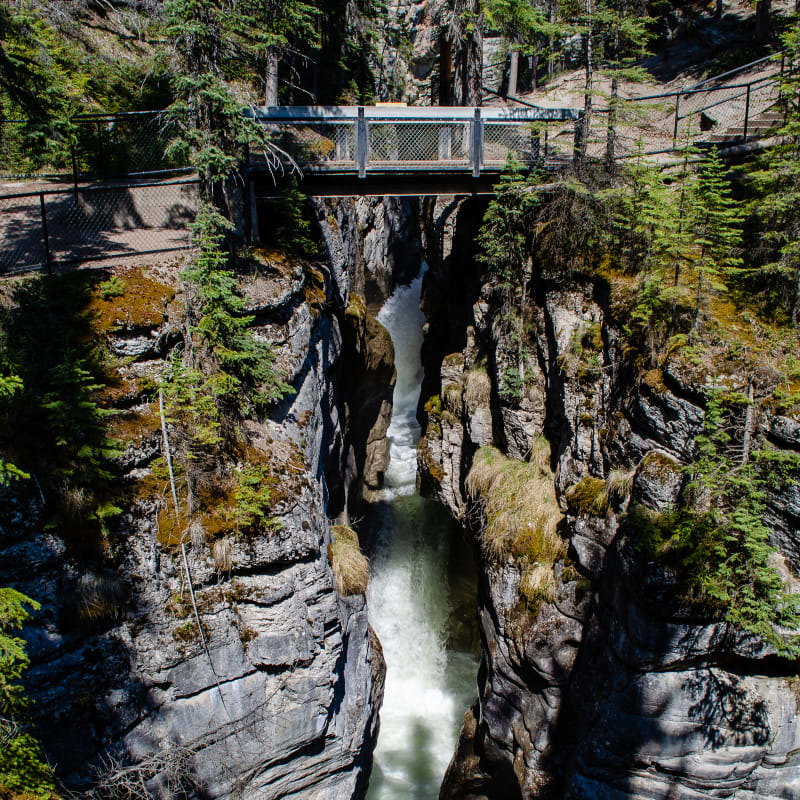 a tall canyon with a bridge on top and a waterfall underneath