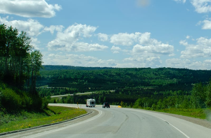 the alaska highway going through rolling hills and green forests