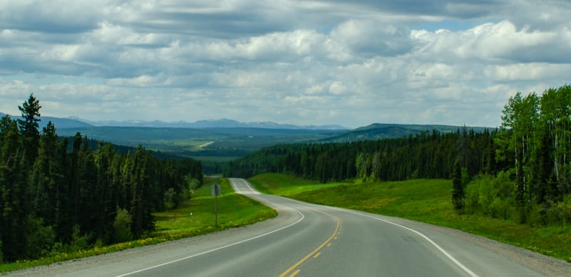 the alaska highway going through rolling hills and green forests with road visibile far in the distance