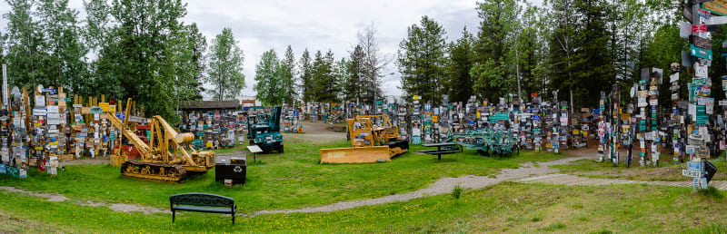 panorama of sign post forest with some historic heavy machinery on display