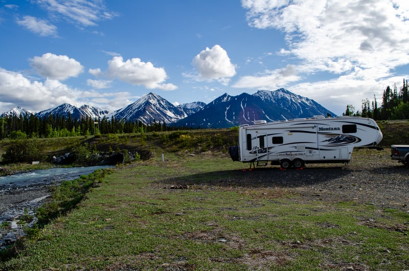 our rv with mountains in the background and a creek running along side