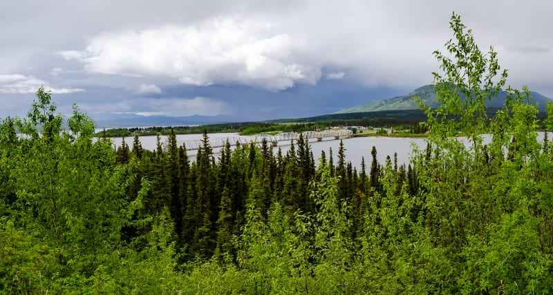 panorama of the bridge leading to teslin, a town on the water