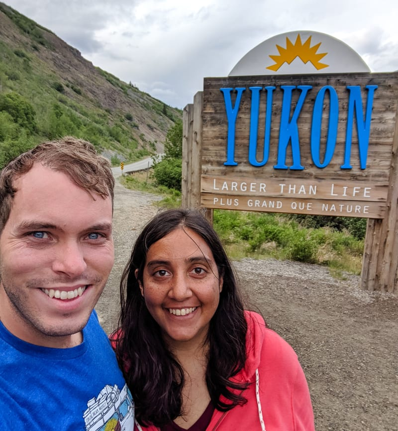 will and sushila by the welcome sign for the yukon