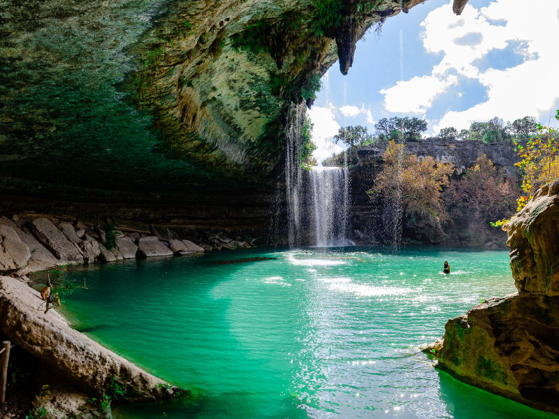 sushila walking through the water at hamilton pool preserve