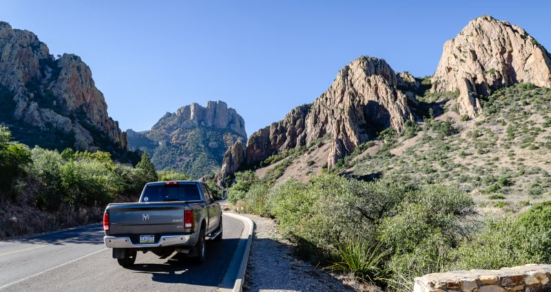mr trucky on the road into chisos basin with mountain peaks ahead