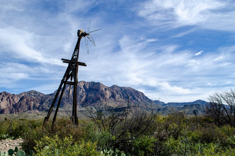an old broken windmill with mountains in the background