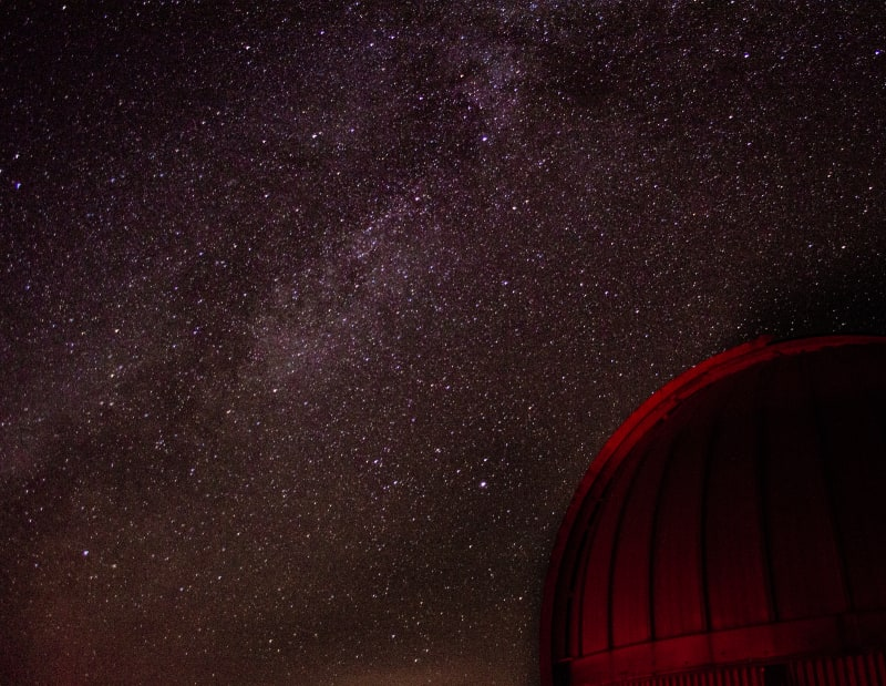 a telescope dome and the milky way in the sky