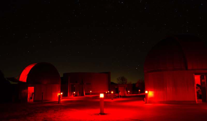 multiple telescope domes with red lights illuminating the area