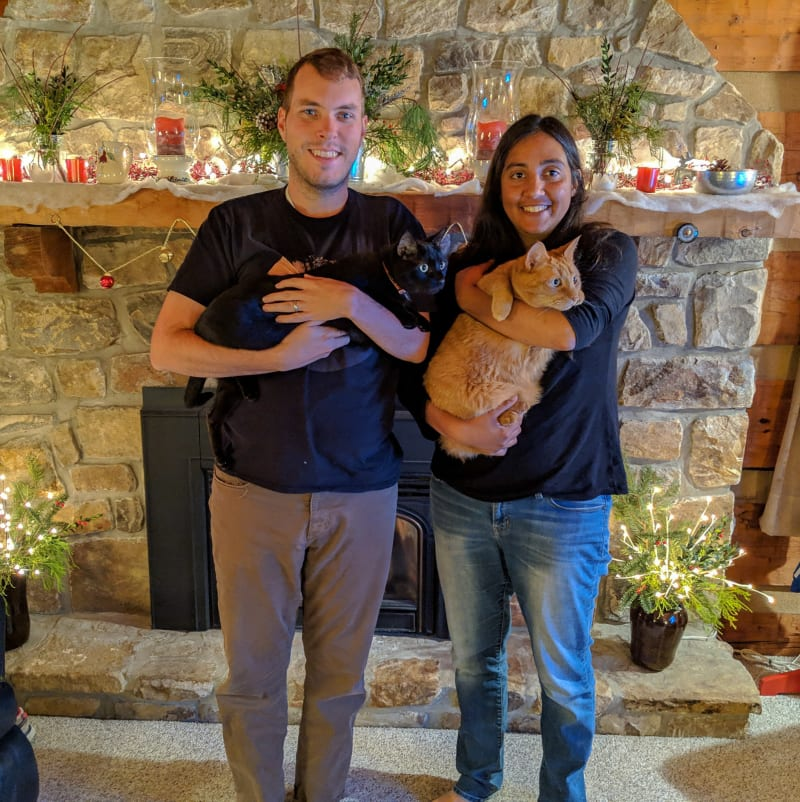 will and sushila holding the cats in front of the fireplace
