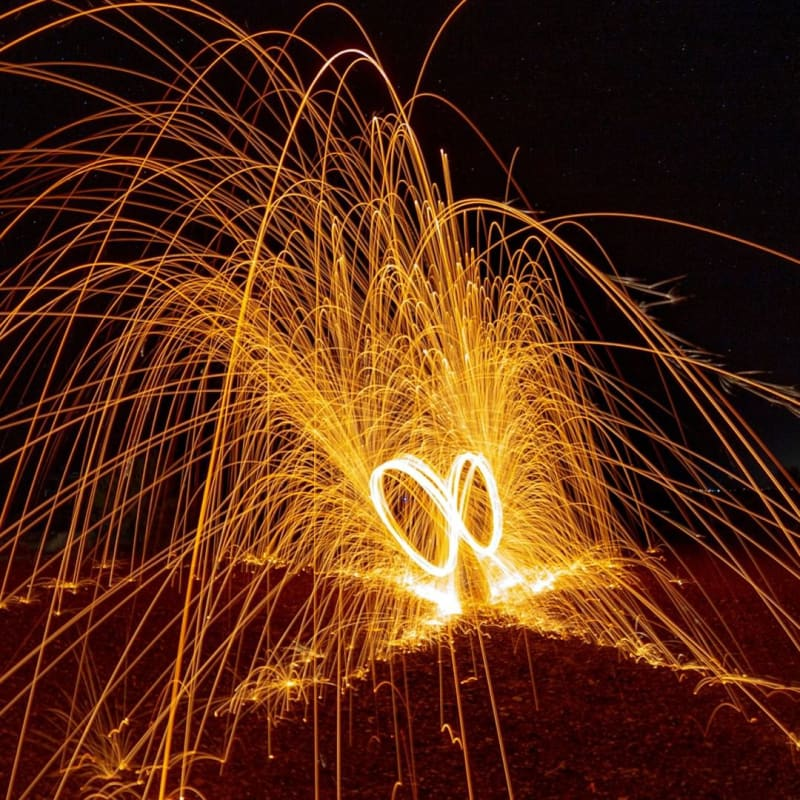 a time-lapse photo of sparks forming an X