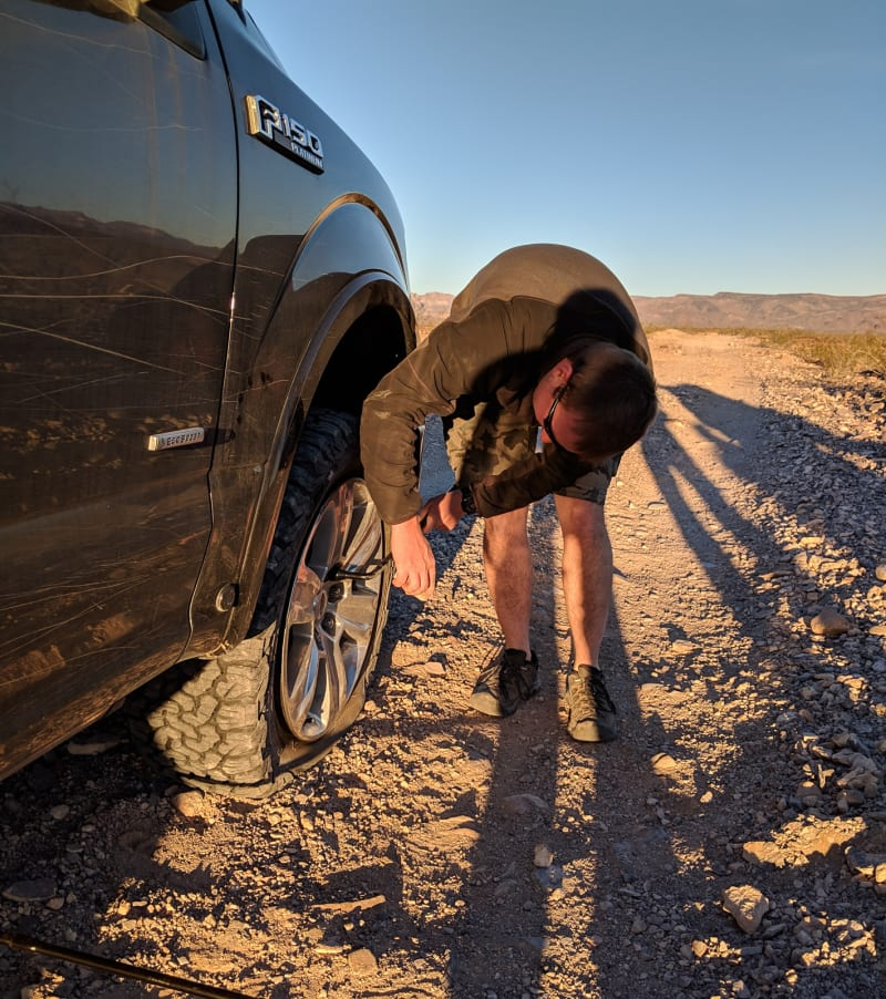 matt looseing the lug nuts on a flat tire