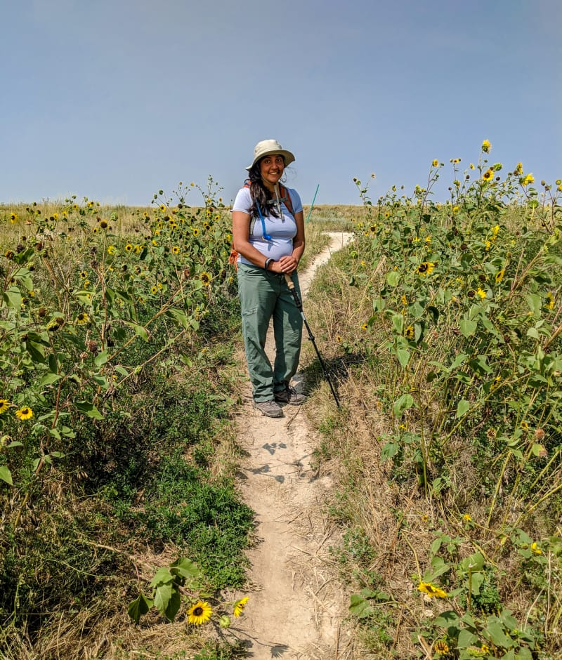 sushila standing in sunflowers on the trail
