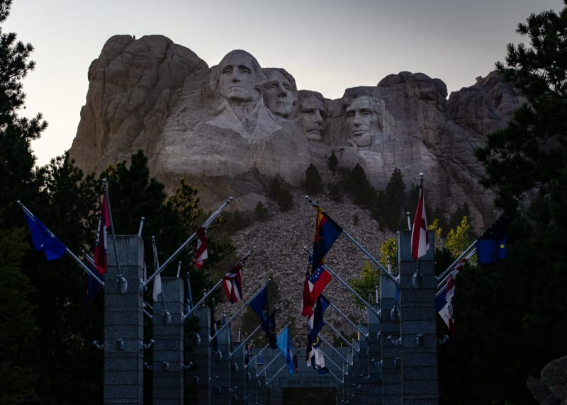 mount rushmore with state flags in foreground