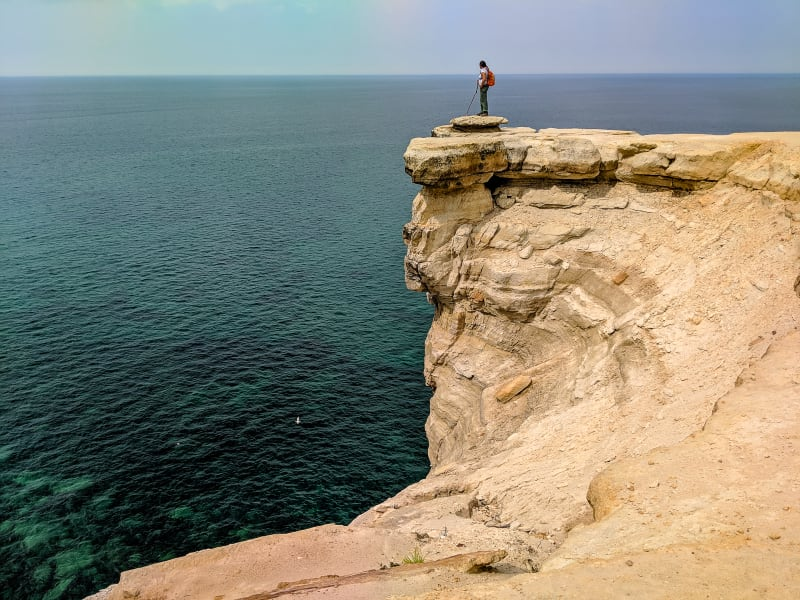 sushila standing on the edge of a cliff looking at the water