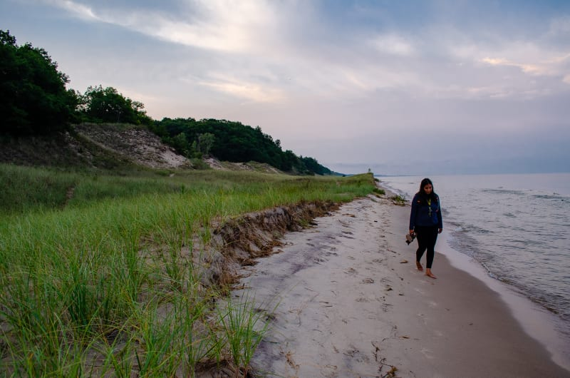 sushila walking along the lakeshore at hoffmaster state park