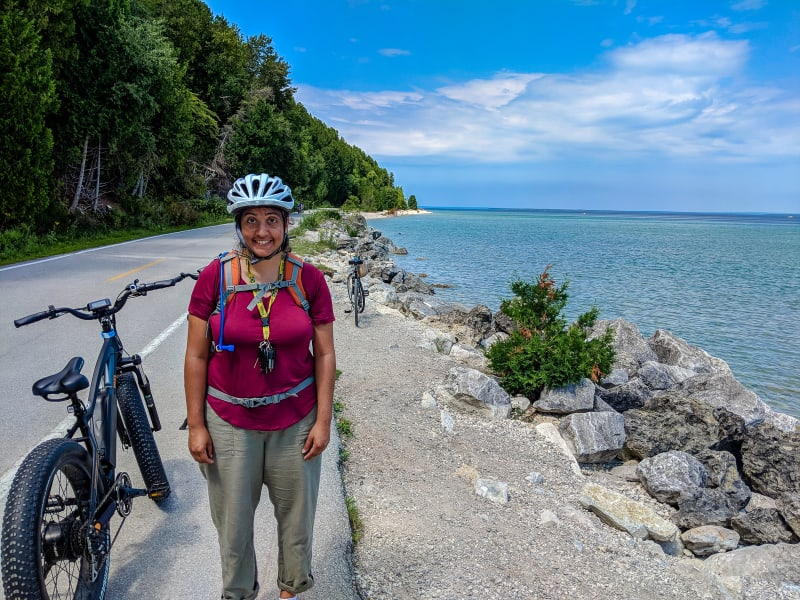 sushila posing with her bike along the shoreline road