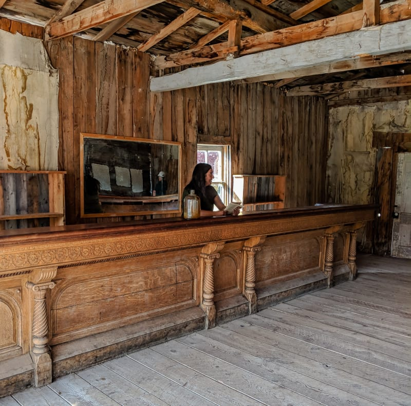 sushila standing behind the bar in one of the buildings