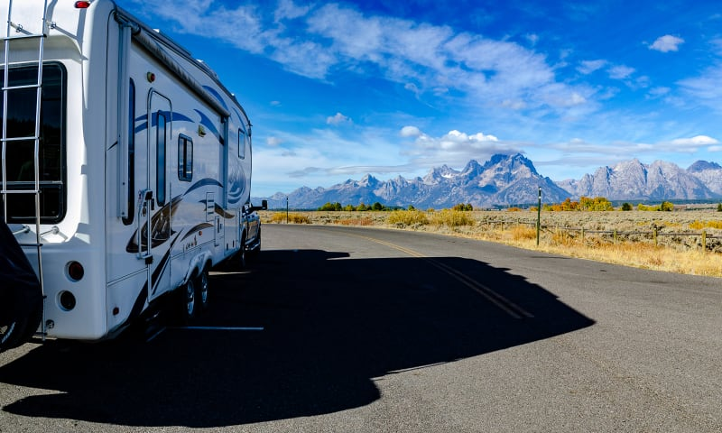 the truck and rv with the teton mountains in the background