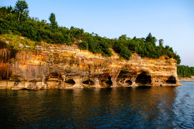 view of colorful limestone cliff at sunset at pictured rocks national lakeshore