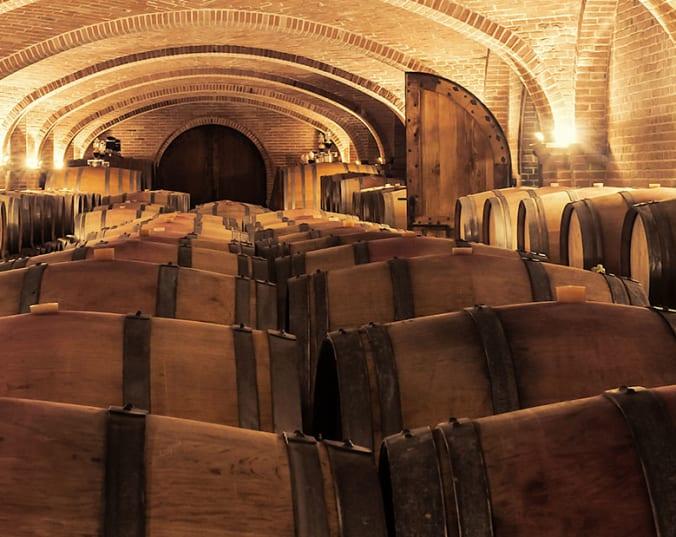 Hier entstehen Weinklassiker: Holzfässer in einem Gewölbe