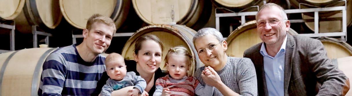 Familie Meier in drei Generationen vor Holzfässern im Weinkeller
