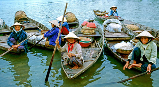 women in conical hats in boats