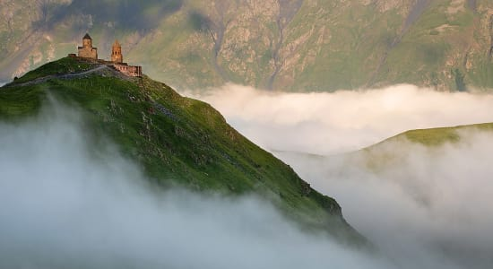 georgia caucasus trek mountain top mist castle