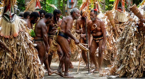 melanesia dancing men in traditional costumes