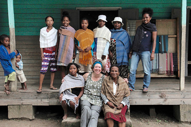 Tourist in Madagascar with local weavers showing handicrafts