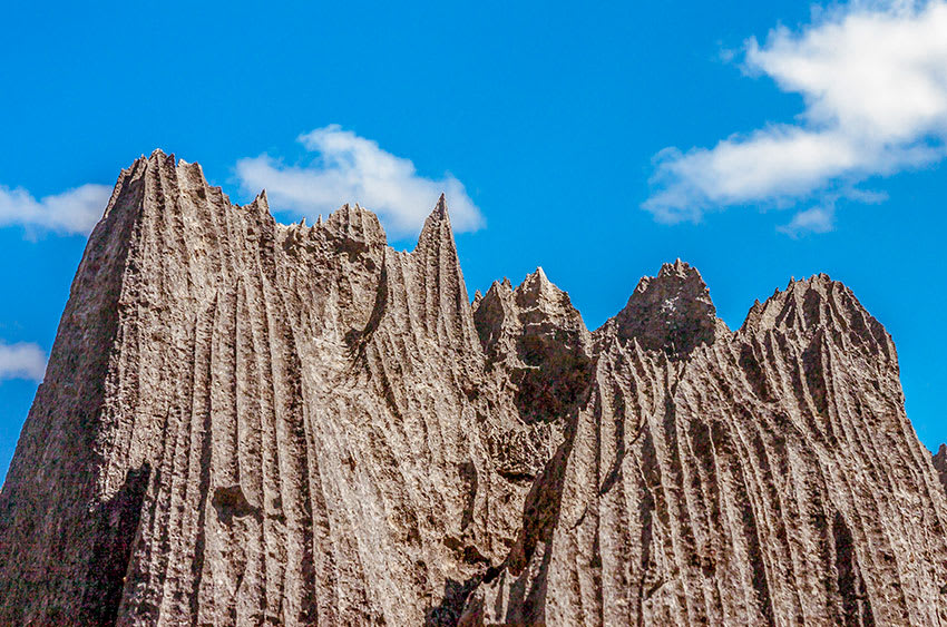 Tsingy limestone pinnacles rise in front of blue sky in Madagascar