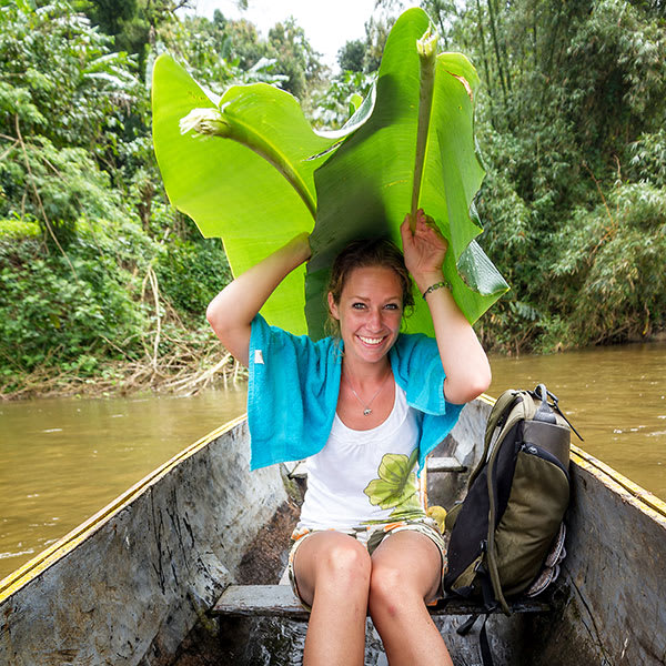 Traveler in canoe using palm fronds as shelter