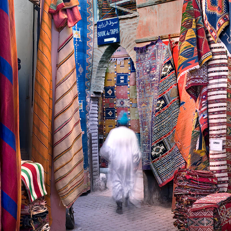 Arab man in white robe and blue truban walking down a narrow pathway lined with colorful hanging Moroccan carpets