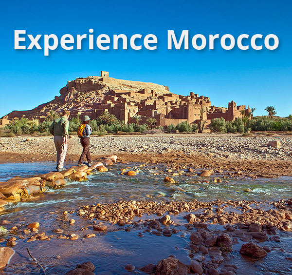 Hikers walking across stream to Moroccan fortress