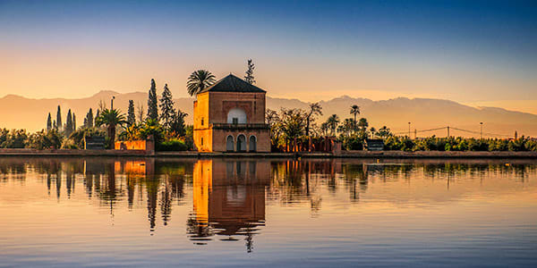 Part of a Moroccan palace surrounded by green trees and reflected in a mirror-like lake, with mountains in background