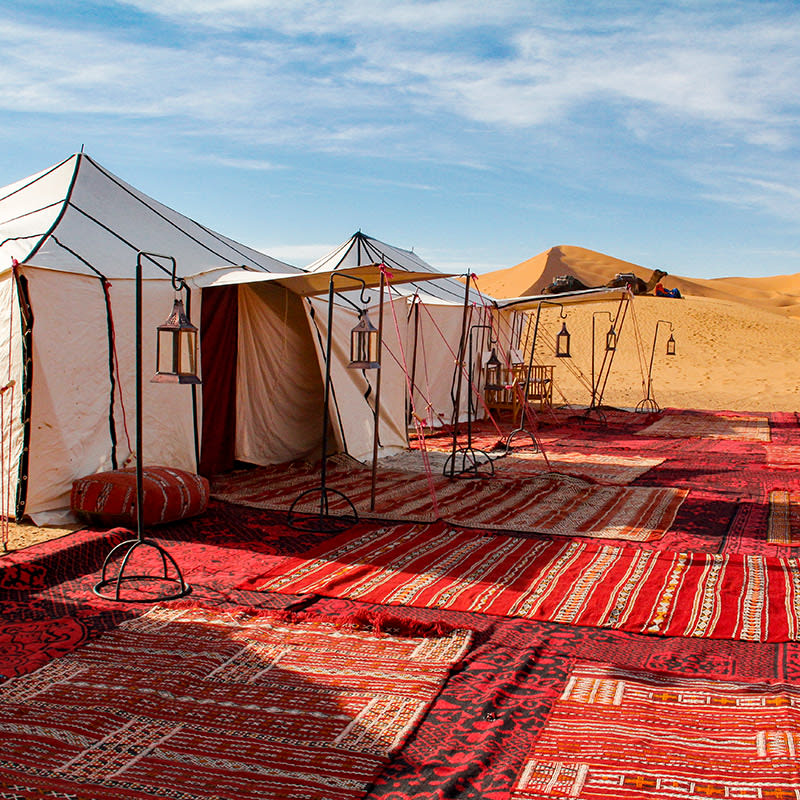 Two white canvas tents with awnings and hanging lanterns, atop many colorful Moroccan rugs in a luxury  desert camp