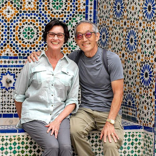 Man and woman traveling couple seated for photo in front of colorful Moroccan geometric tilework