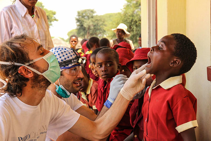 Dentists checking teeth of children in Zimbabwe village