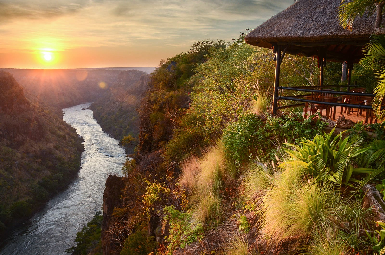 Open-air veranda at Gorges Lodge overlooking sunset above Batoka Gorge in Zimbabwe
