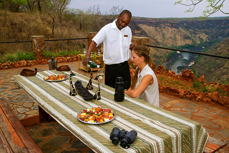 Waiter pouring wine for traveler sitting on deck by river in Zimbabwe