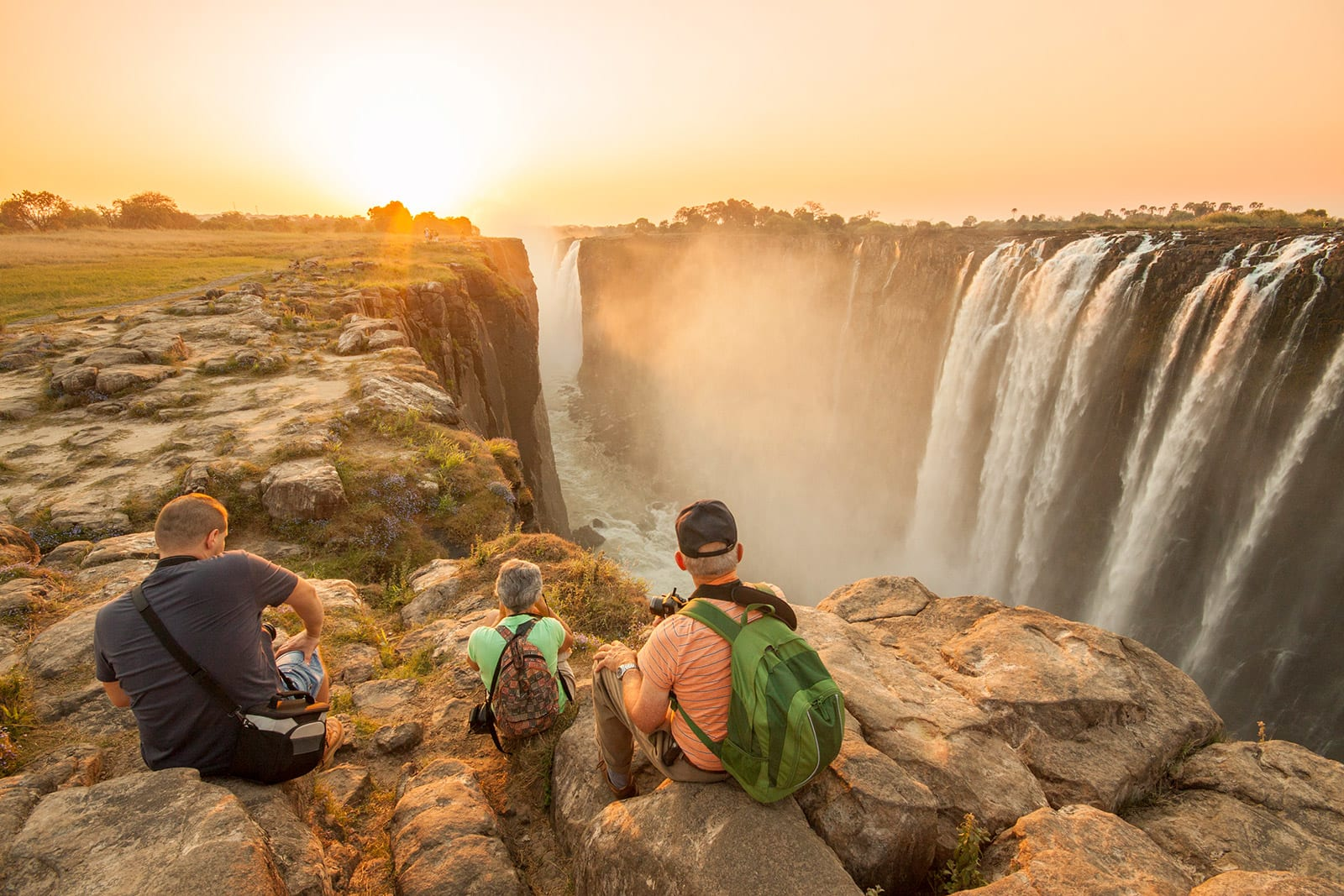 Three travelers sitting by Victoria Falls at sunset