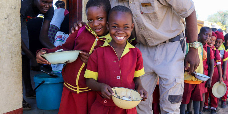 Teacher smiling with students who are waiting in line for food at school in Zimbabwe
