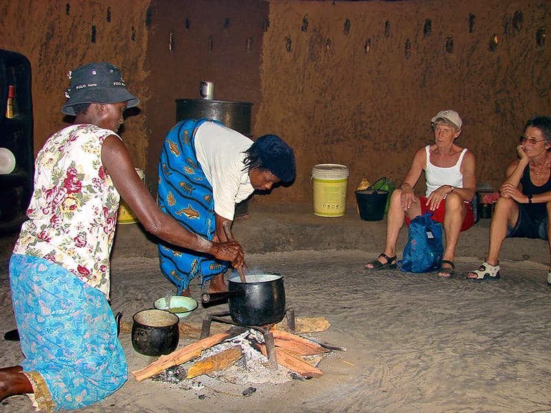 Travelers watching women cook food over fire in Zimbabwe