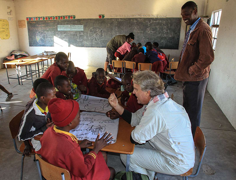 Traveler sitting with group of students in their classroom in Zimbabwe