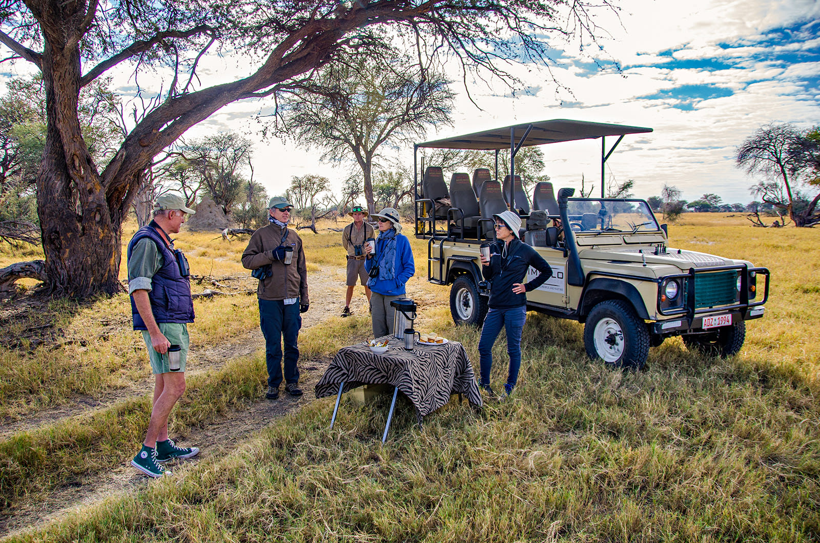 Group of travelers having coffee by safari jeep in Zimbabwe