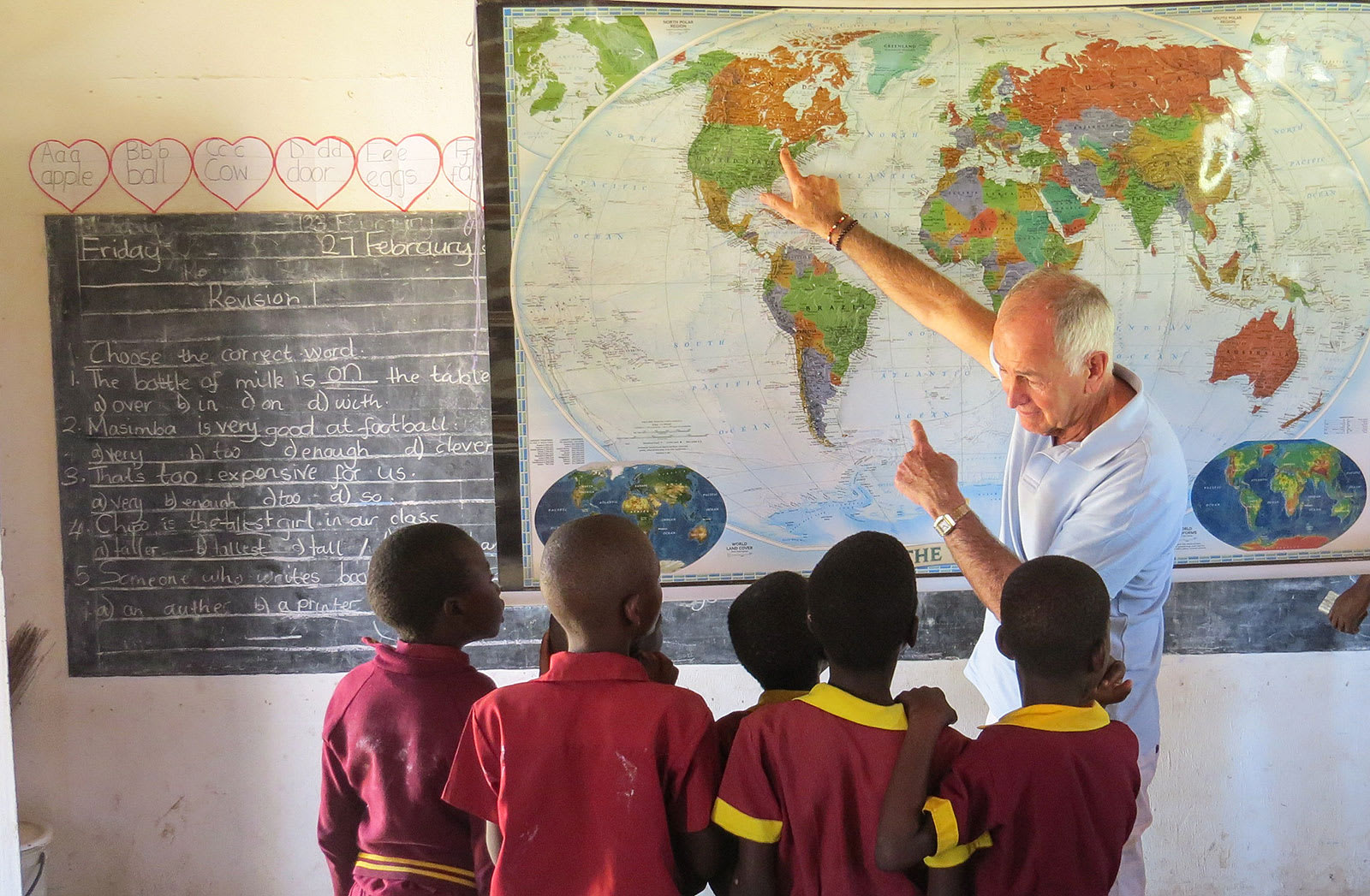 Traveler pointing to a world map in Zimbabwe school room